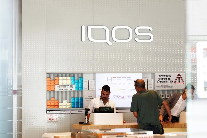 Shop attendants serve a customer at a Philip Morris iQOS store in Tel Aviv