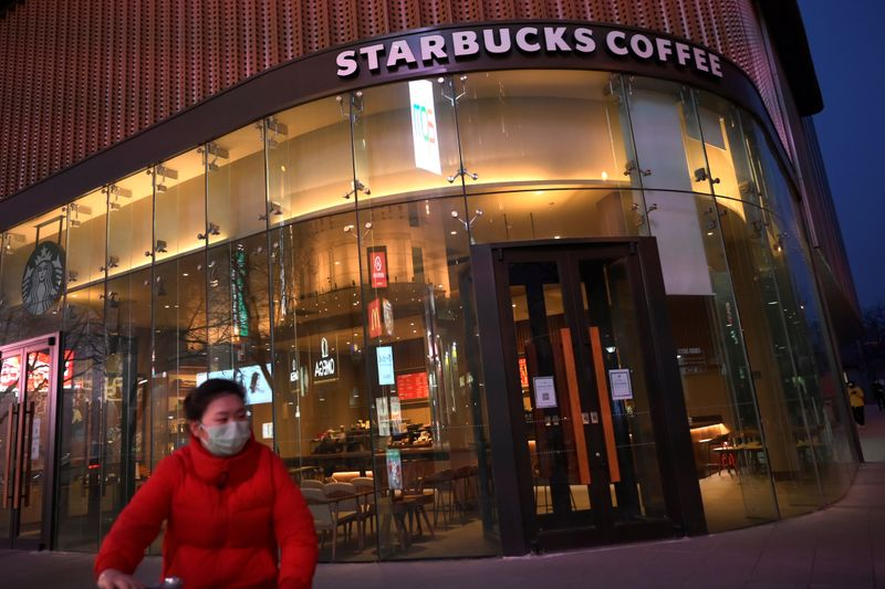 Woman wearing a face mask rides a bicycle past a Starbucks coffee store, as the country is hit by an outbreak of the novel coronavirus, in Beijing
