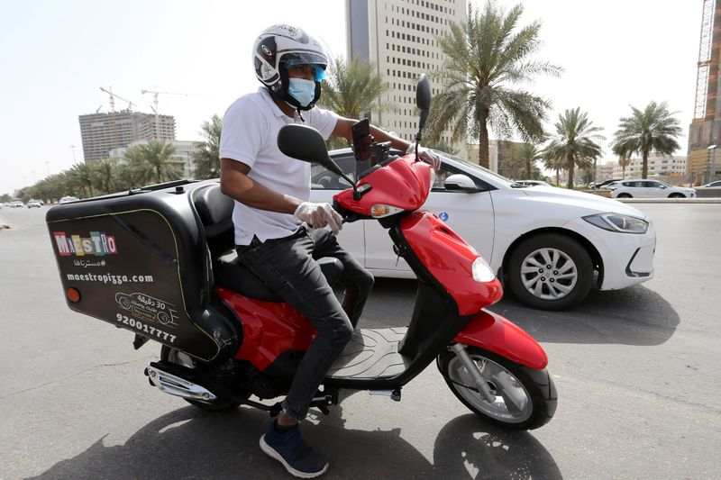 A delivery man rides his motorbike to deliver food orders for customers, as restaurants are closed, following the outbreak of coronavirus, in Riyadh
