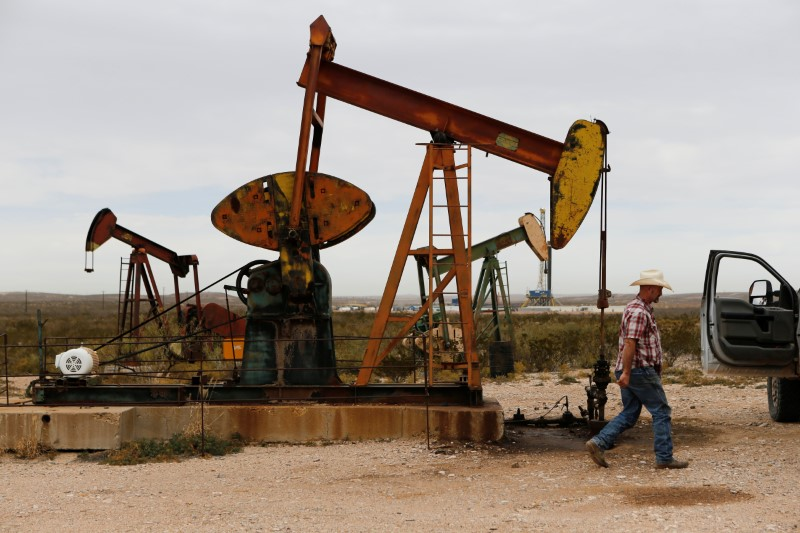 Paul Putnam, 53, a rancher and independent contract pumper walks past a pump jack in Loving County