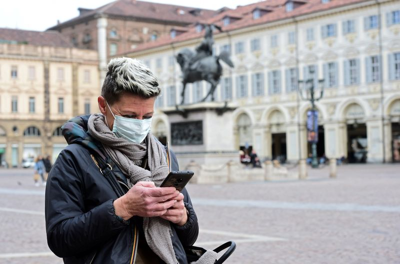 FILE PHOTO: Woman wearing a protective mask uses her mobile phone, as a coronavirus outbreak continues to grow in northern Italy, in Turin