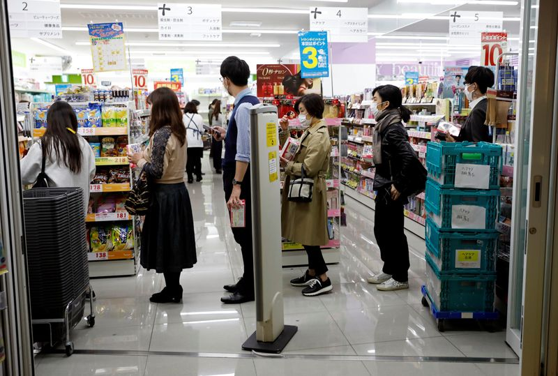 People wearing protective face masks following an outbreak of the coronavirus disease queue to buy masks at a drugstore in Tokyo, Japan