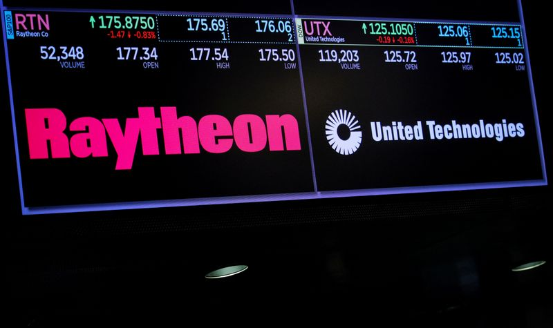 A screen shows the logos and trading information for defense contractor Raytheon Co, and United Technologies Corp. on the floor at the NYSE in New York
