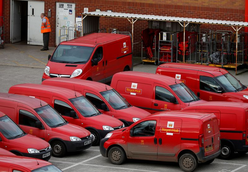 FILE PHOTO: A Royal Mail postal worker stands in the yard of a sorting office in Altrincham,