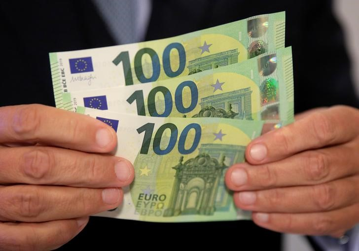 An Austrian central bank official displays new 100 euro banknotes in Vienna