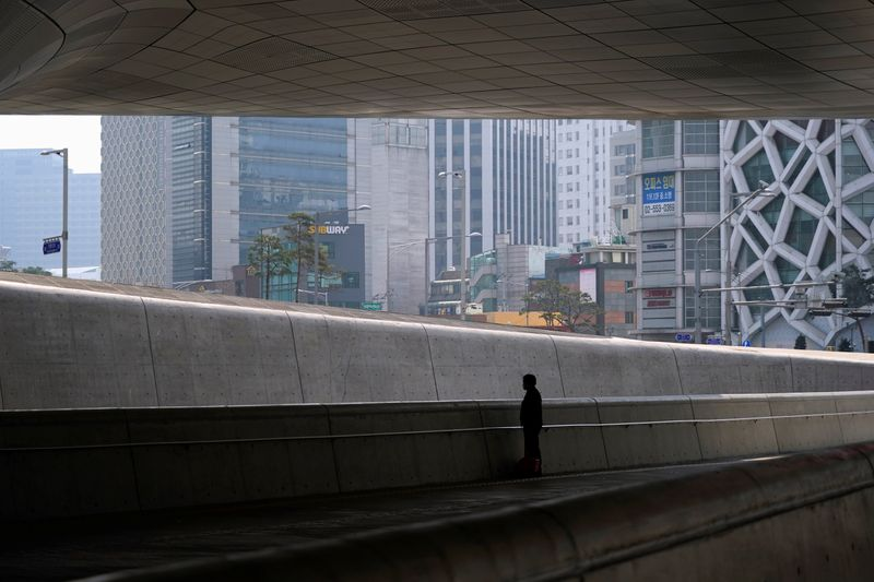 A cleaner wearing a mask to prevent contracting the coronavirus disease (COVID-19) stands along an empty street in Seoul, South Korea