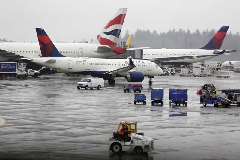 FILE PHOTO: Delta Airlines planes and a British Airways plane are pictured at Seattle-Tacoma International Airport in SeaTac, Washington