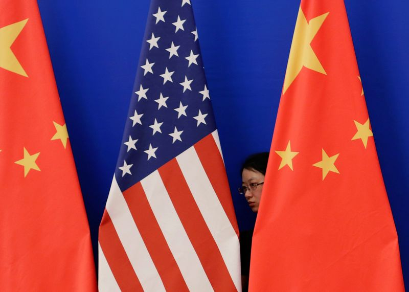 FILE PHOTO: A member of staff from Chinese government adjusts U.S. and Chinese national flags in Beijing