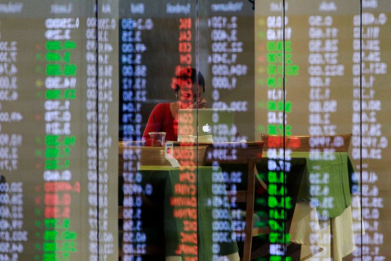 Philippine Stock Exchange share prices are reflected on a glass panel as broker takes a break in Manila