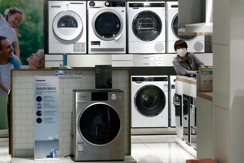 FILE PHOTO: A woman wearing a protective mask looks at products at a home appliances retailer in Beijing