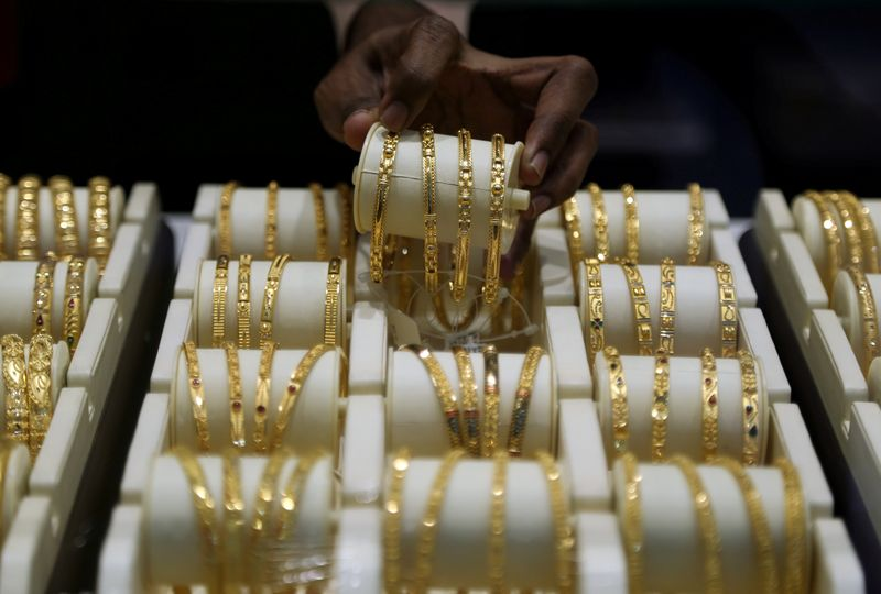 FILE PHOTO: A salesman arranges gold bangles inside a jewellery showroom on the occasion of Akshaya Tritiya, a major gold buying festival, in Mumbai, India