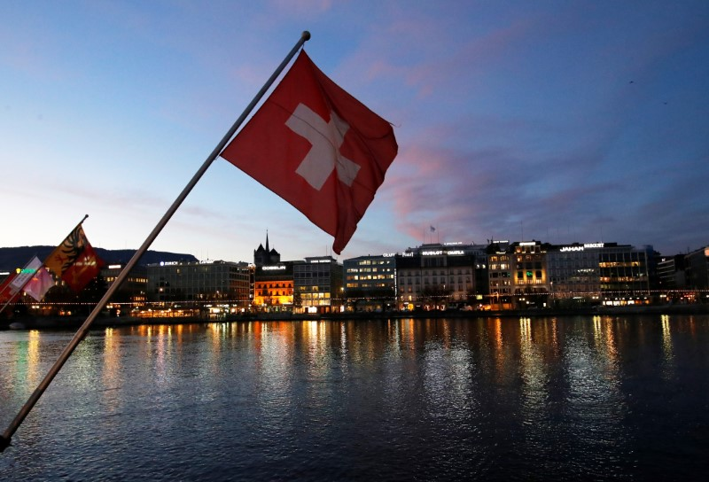A Swiss flag is pictured during the sunrise on the Commercial and Financial District in Geneva