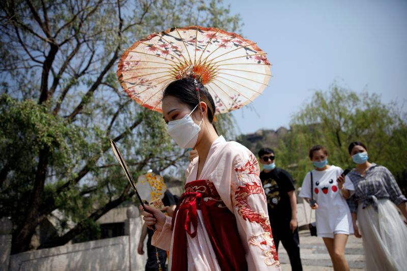 FILE PHOTO: A woman wearing face mask and traditional Chinese clothing visits Gubei Water Town on the first day of the five-day Labour Day holiday, following the coronavirus disease (COVID-19) outbreak, on the outskirts of Beijing