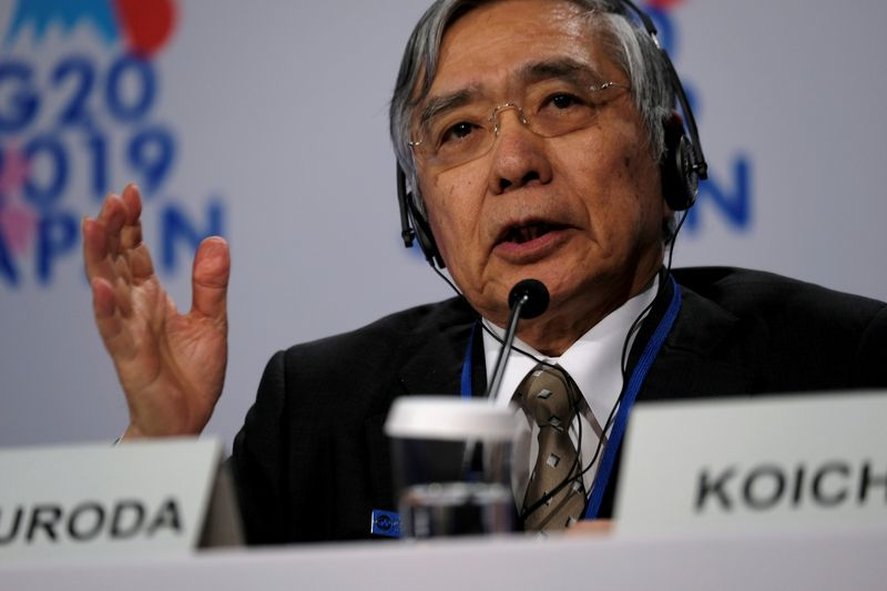FILE PHOTO: Bank of Japan Governor Haruhiko Kuroda takes questions from reporters at the annual meetings of the International Monetary Fund and World Bank in Washington