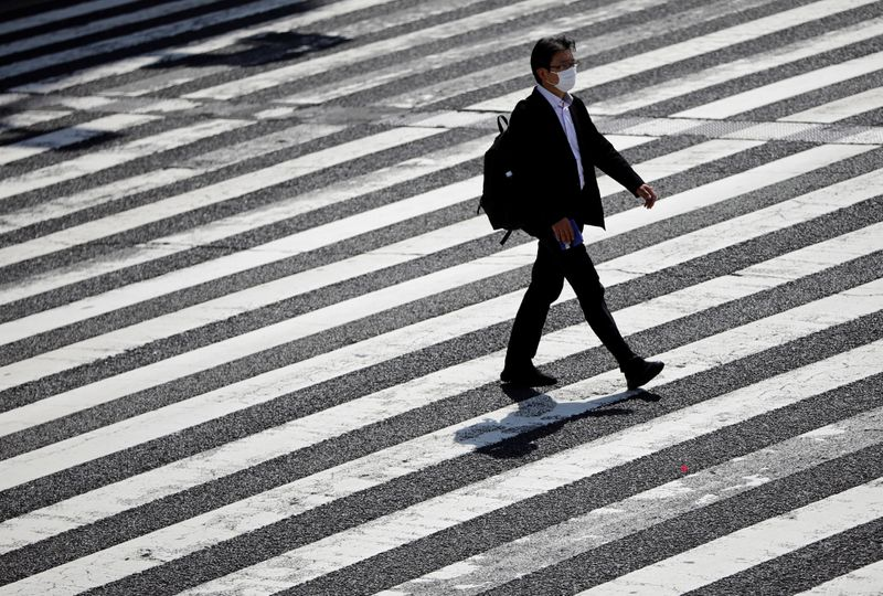 A businessman wearing a protective face mask walks on the crossing as the spread of the coronavirus disease (COVID-19) continues in Tokyo, Japan