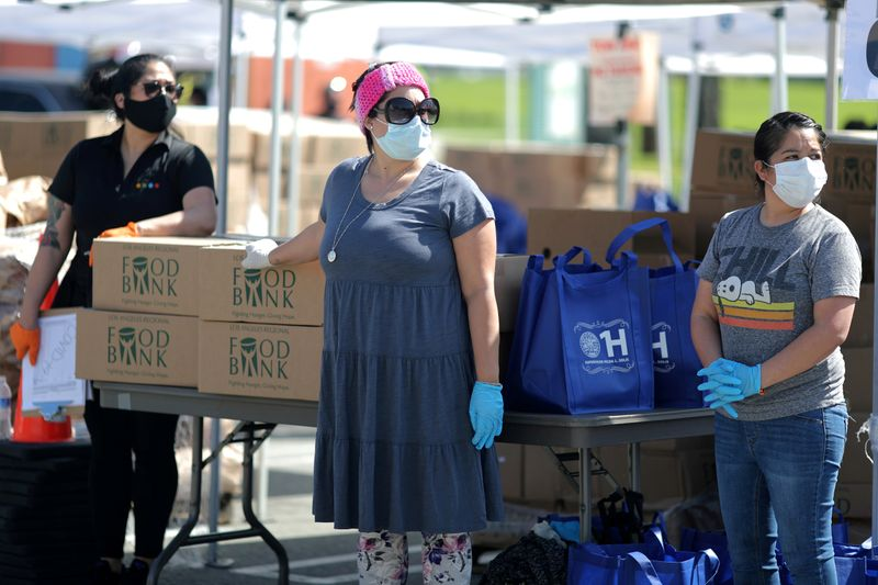 FILE PHOTO: Volunteers at Los Angeles Food Bank hand out supplies at a drive-through food giveaway as the global outbreak of coronavirus disease (COVID-19) continues, in Los Angeles