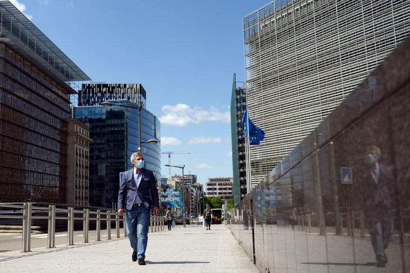 FILE PHOTO: A man wearing a face mask walks past the European Commission headquarters as the spread of coronavirus disease (COVID-19) continues in Brussels