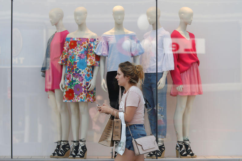 FILE PHOTO:  A woman carries shopping bags while walking past a window display outside a retail store in Ottawa