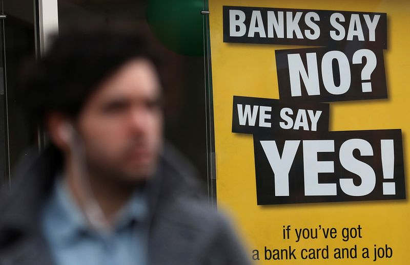 FILE PHOTO: A pedestrian walks past a payday lending shop in London