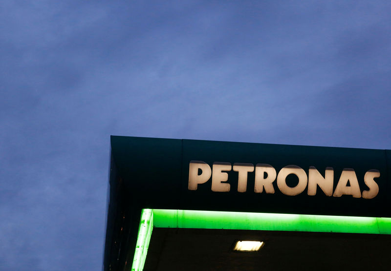 The sign of a Petronas fuel station is seen against a darkening sky in Kuala Lumpur