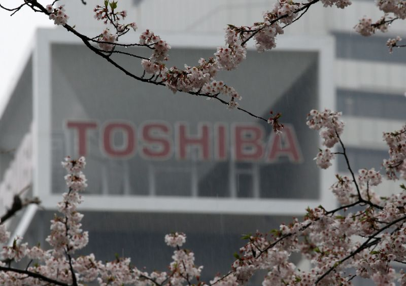 FILE PHOTO: The logo of Toshiba Corp is seen behind cherry blossoms at the company's headquarters in Tokyo