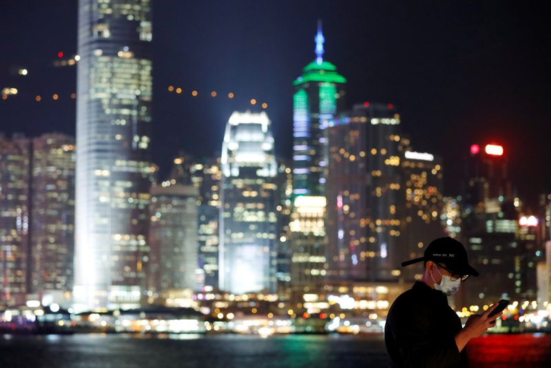 FILE PHOTO: A man wears mask to prevent a new coronavirus outbreak as he uses his mobile, with skyline in the background of Hong Kong