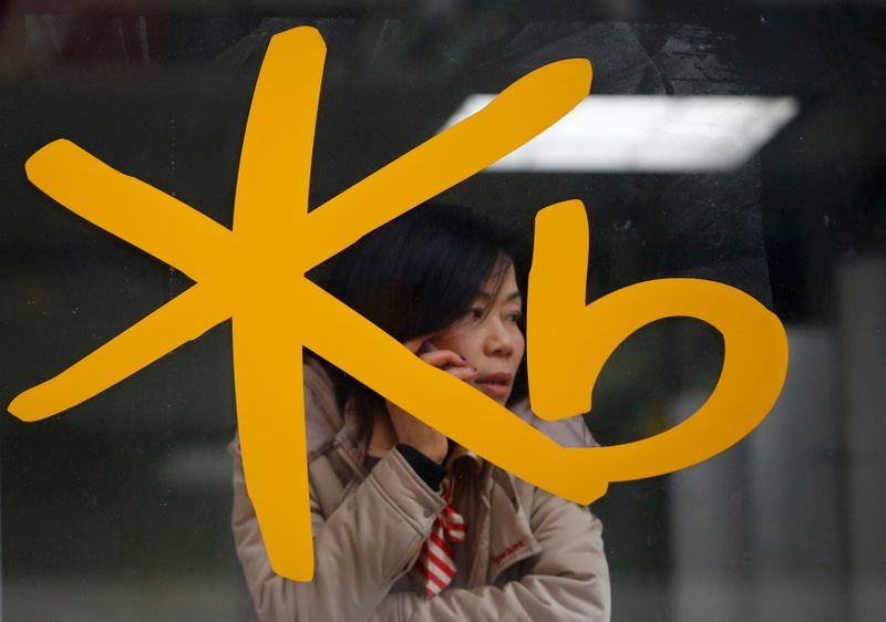 A customer talks on the phone behind the logo of KB Kookmin Financial Group at a branch of KB Kookmin Bank in Seoul