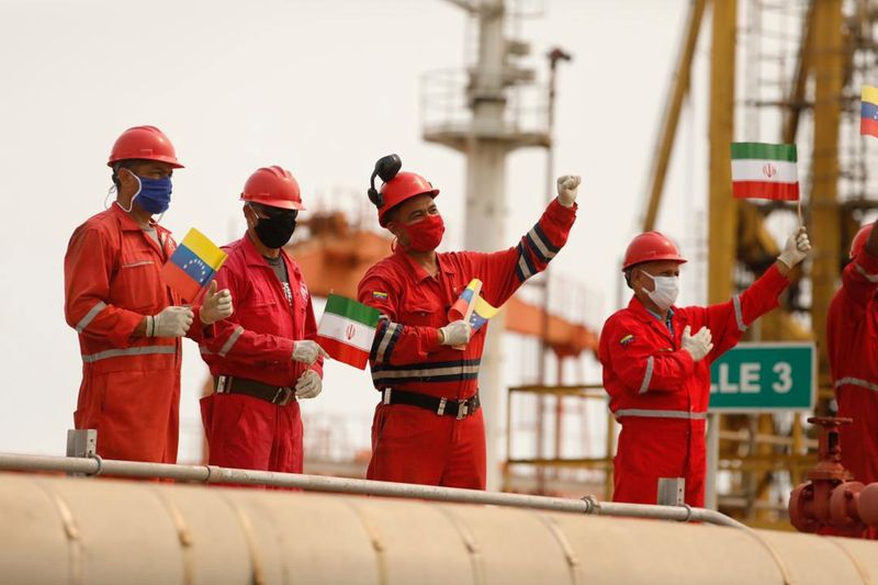 FILE PHOTO: Workers of the state-oil company Pdvsa holding Iranian and Venezuelan flags greet during the arrival of the Iranian tanker ship