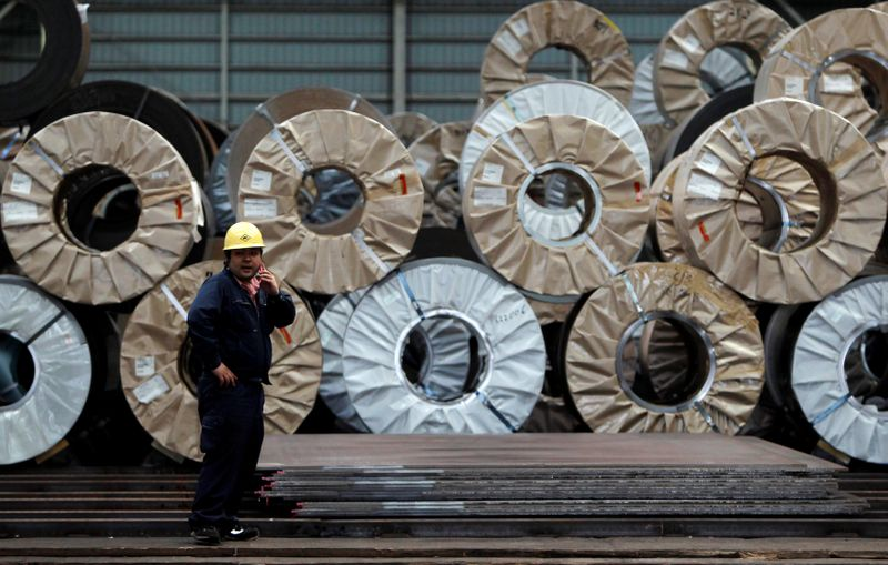 A worker uses a mobile phone in front of steel coils and steel sheets at a distribution warehouse in Urayasu