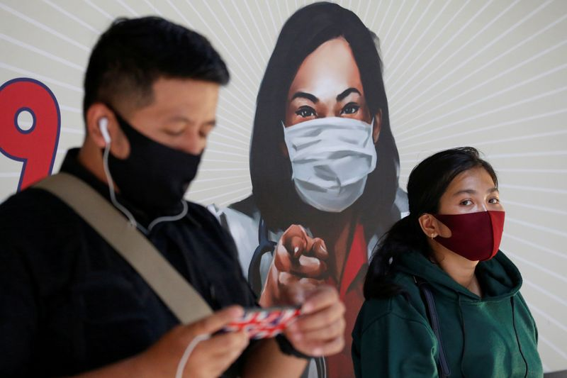 FILE PHOTO: People are seen wearing protective face masks at a station in Jakarta, Indonesia