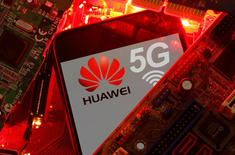 A smartphone with the Huawei and 5G network logo is seen on a PC motherboard in this illustration