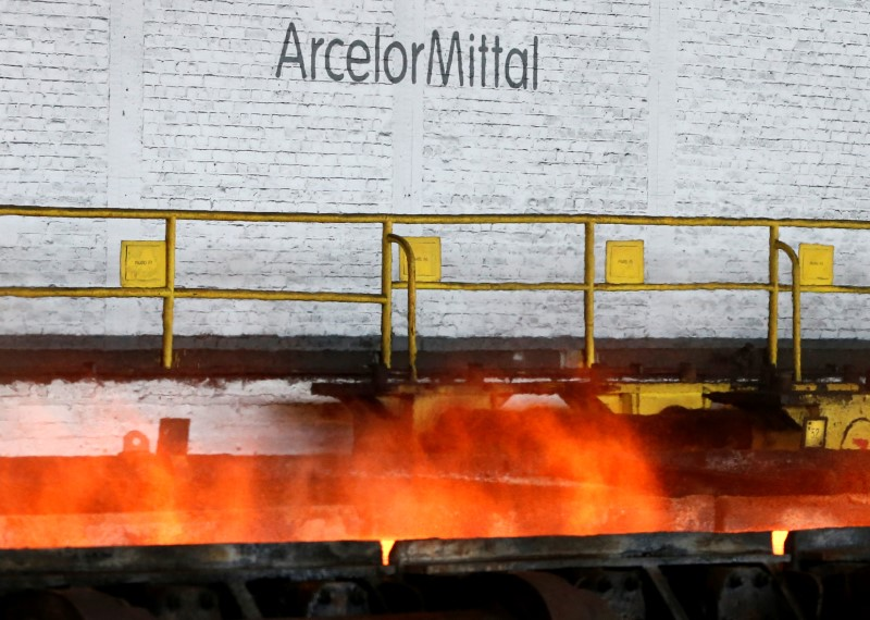 FILE PHOTO: The logo of ArcelorMittal is pictured in front of heat rising from a red-hot steel plate at the ArcelorMittal steel plant in Ghent