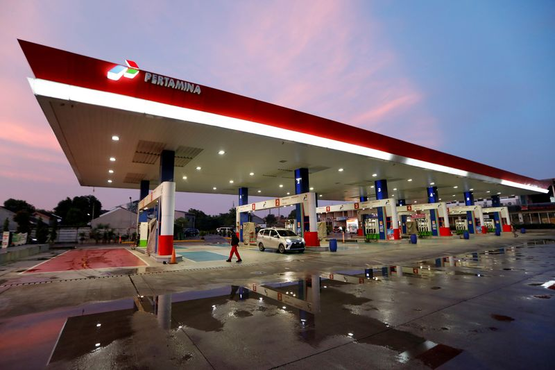 FILE PHOTO: Worker walks past a car at a state-owned Pertamina petrol station in Bekasi, on the outskirts of Jakarta