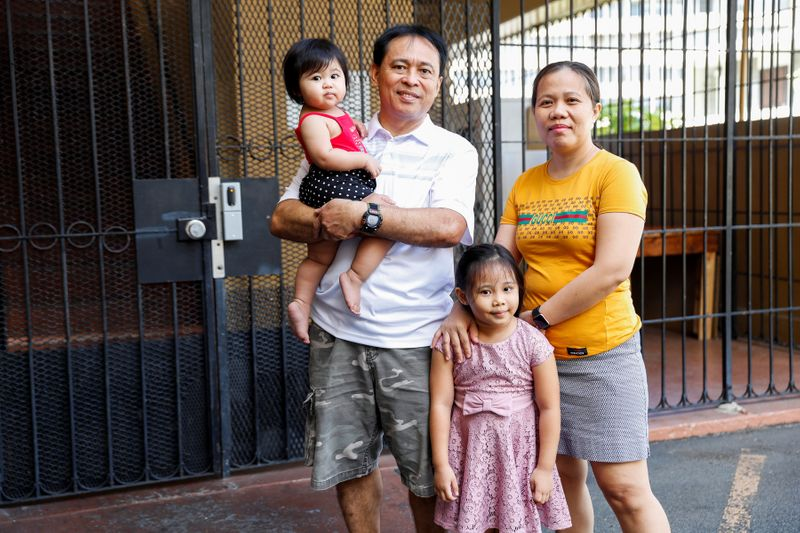 Judith and Jose Ramirez pose with their daughters outside their home in Honolulu