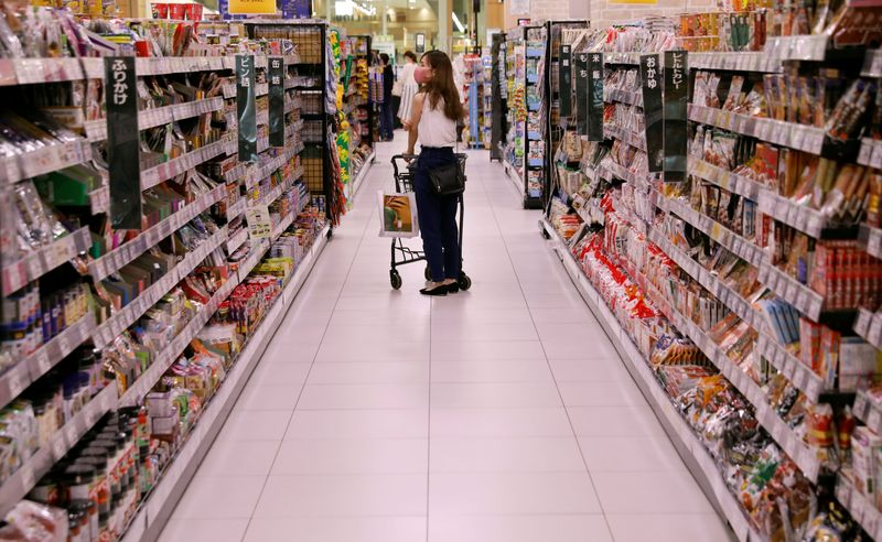 FILE PHOTO: A shopper wearing a protective mask pushes a shopping cart at Japan's supermarket group Aeon's shopping mall as the mall reopens amid the coronavirus disease (COVID-19) outbreak in Chiba