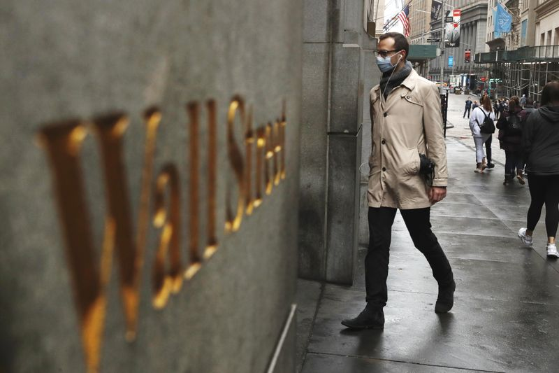 FILE PHOTO: A man wears a protective mask as he walks on Wall Street during the coronavirus outbreak in New York