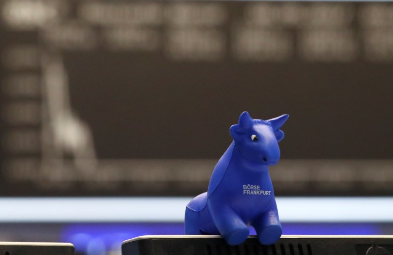 A plastic bull figurine, symbol of the Frankfurt stock exchange is pictured in front of the share price index DAX board at the stock exchange in Frankfurt