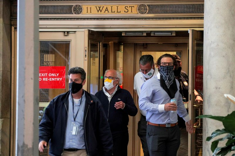 Traders exit the 11 Wall St. door of the NYSE in New York