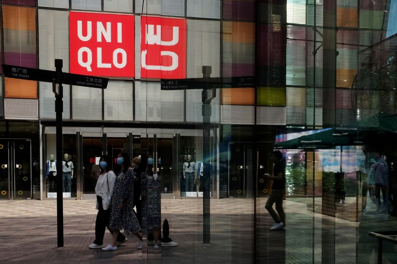 FILE PHOTO: Women walk past a store of the Fast Retailing's fashion chain Uniqlo, in Beijing