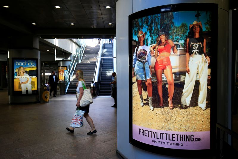 A shopper walks pass advertising billboards for Boohoo and for 'Pretty Little Things', a Boohoo brand, at Canary Wharf DLR station in central London