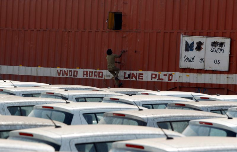 A worker climbs a container to close its window after unloading cars at a warehouse on outskirts of Ahmedabad