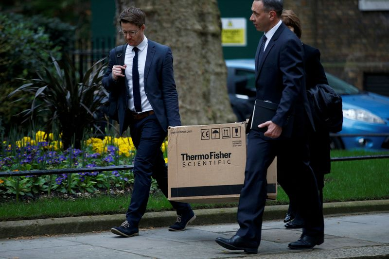 FILE PHOTO: People carrying a box from ThermoFisher Scientific, a company that produces coronavirus tests, walk outside Downing Street in London
