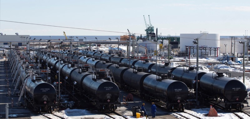FILE PHOTO: Irving Oil workers inspect rail cars carrying crude oil at the Irving Oil rail yard terminal in Saint John, New Brunswick