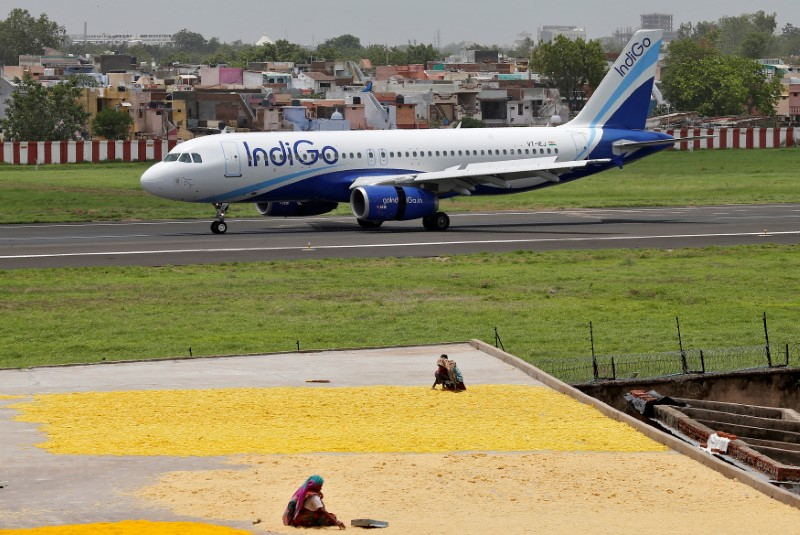 Women spread fryums for drying on a rooftop as an IndiGo Airlines Airbus A320 aircraft moves on the runway after landing at the Sardar Vallabhbhai Patel international airport in Ahmedabad