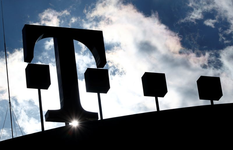 The logo of Deutsche Telekom AG is silhouetted against the sun and clouds atop of the headquarters of German telecommunications giant in Bonn