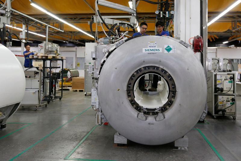 FILE PHOTO: Staff work on magnetic resonance imaging machines at a production line of Siemens Healthineers in Shenzhen