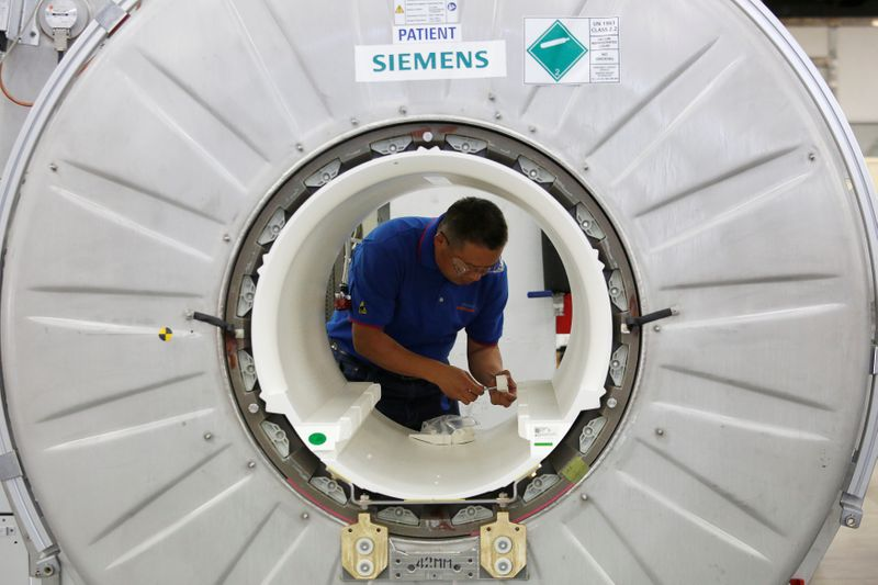 A staffer works on a magnetic resonance imaging machine at a production line of Siemens Healthineers in Shenzhen