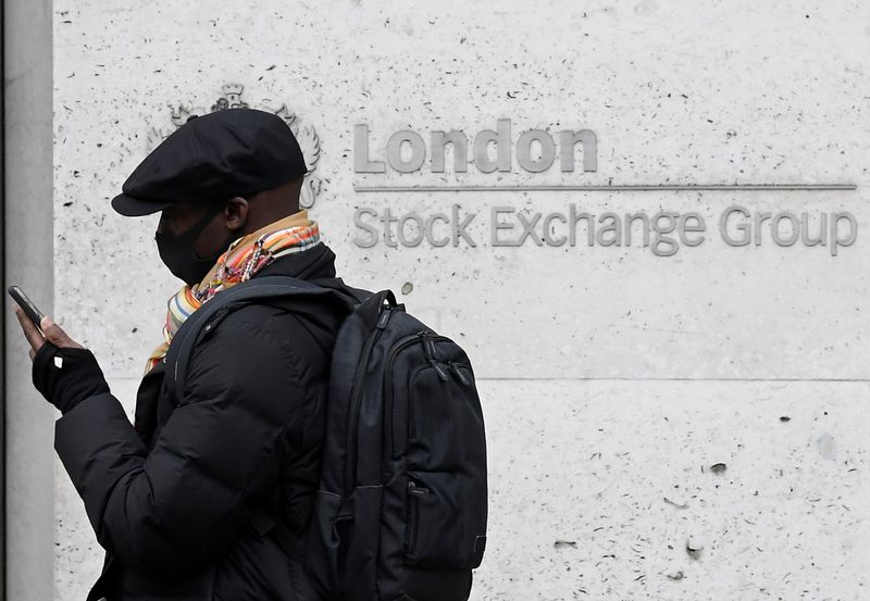 FILE PHOTO: A man wearing a protective face mask walks past the London Stock Exchange Group building in the City of London financial district, whilst British stocks tumble as investors fear that the coronavirus outbreak could stall the global economy