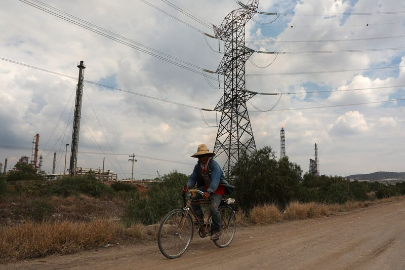 A man rides a bike on a road near high-voltage transmission lines near the Tula power plant owned by state-owned power company Comisión Federal de Electricidad, or CFE, in Tula de Allende