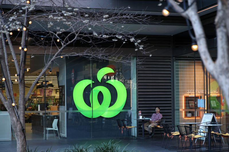 A man sits outside a Woolworths supermarket in Sydney
